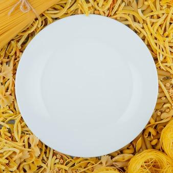 Vista dall'alto del piatto bianco su pasta cruda di diverse forme e tipi come su sfondo