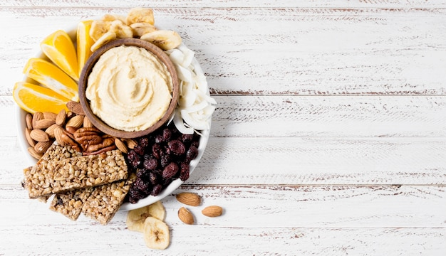 Vista dall'alto del piatto con assortimento di noci e barrette di cereali con spazio di copia