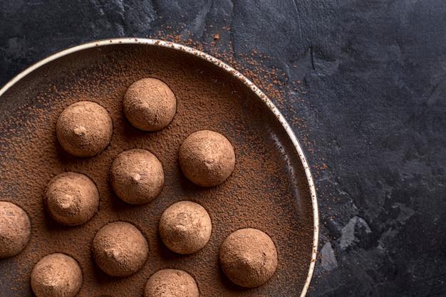 Vista dall'alto del piatto con caramelle al cioccolato e cacao in polvere