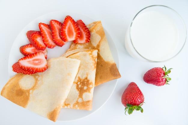Vista dall'alto del piatto con sottili crepes con fettine di fragola e latte. la colazione estiva piatta giaceva sullo sfondo bianco