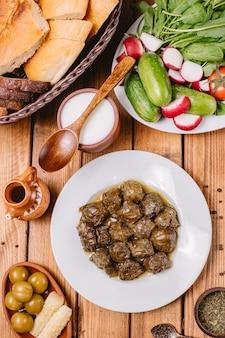 Vista dall'alto del piatto di dolma azero foglie d'uva servito con yogurt e insalata