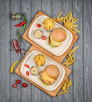 Vista dall'alto del piatto di fast food. hamburger di carne, patatine fritte e spicchi.