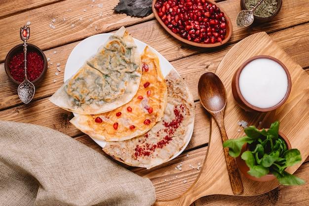Vista dall'alto del piatto di gutab azero con erbe zucca e carne servita con yogurt