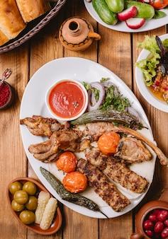 Vista dall'alto del piatto di kebab con pollo verdure agnello tikka e spiedini di lula