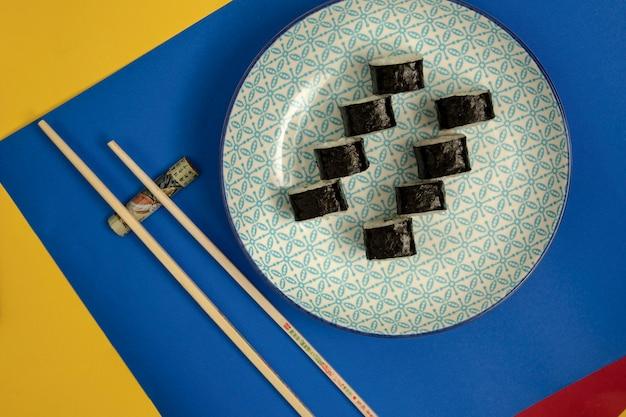 Vista dall'alto del piatto di rotoli di sushi nori, bacchette su sfondo blu e giallo