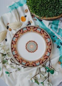Vista dall'alto del piatto orientale in ceramica con un modello nazionale con shekerbura e semeni sul muro di sciarpa femminile di seta kelagai tradizionale bianco