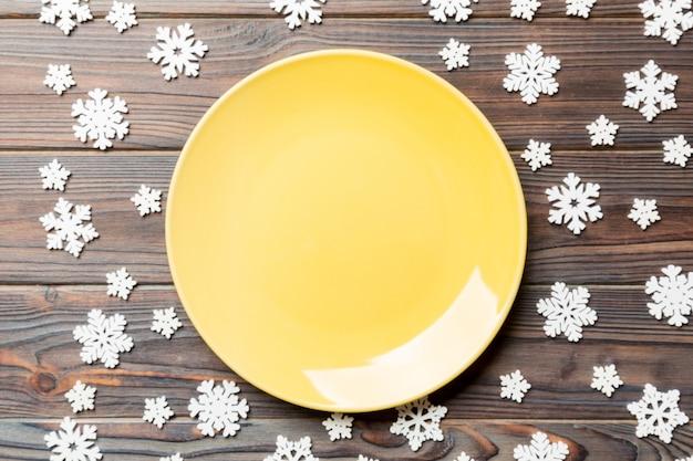 Vista dall'alto del piatto vuoto circondato con fiocchi di neve su legno