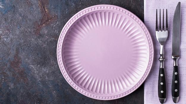 Vista dall'alto del piatto vuoto, coltello e forchetta. dieta e concetto sano. spazio per il testo
