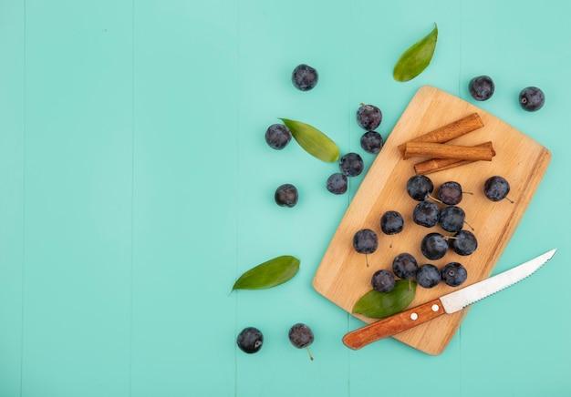 Vista dall'alto del piccolo aspro frutto nerastro prugnole su una tavola da cucina in legno con bastoncini di cannella con coltello su uno sfondo blu con spazio di copia