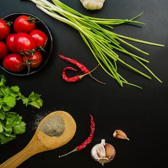 Vista dall'alto del pomodoro; peperoncini rossi; cipollotto; aglio; prezzemolo e spezie su sfondo nero