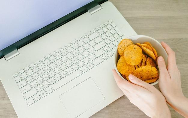Vista dall'alto del portatile e mani femminili con patatine