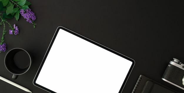 Vista dall'alto del posto di lavoro alla moda fotografo con tablet schermo vuoto e forniture per ufficio