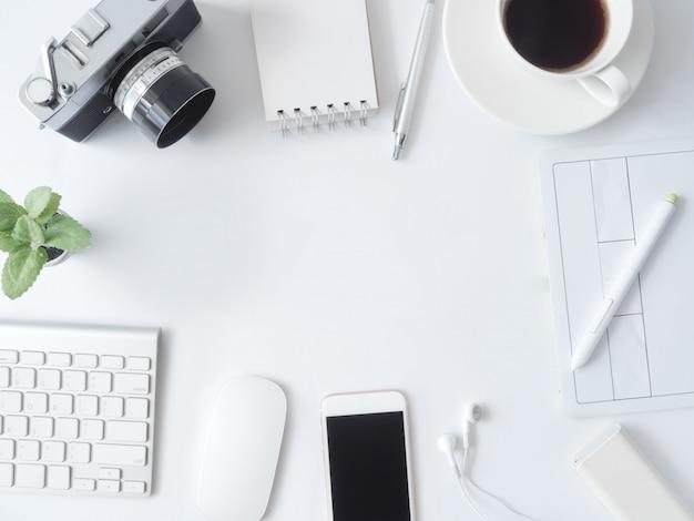 Vista dall'alto del posto di lavoro con tazza di caffè, notebook, pianta in plastica, smartphone e tastiera sul tavolo