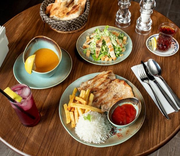 Vista dall'alto del pranzo con pollo alla griglia e zuppa di lenticchie di riso e insalata