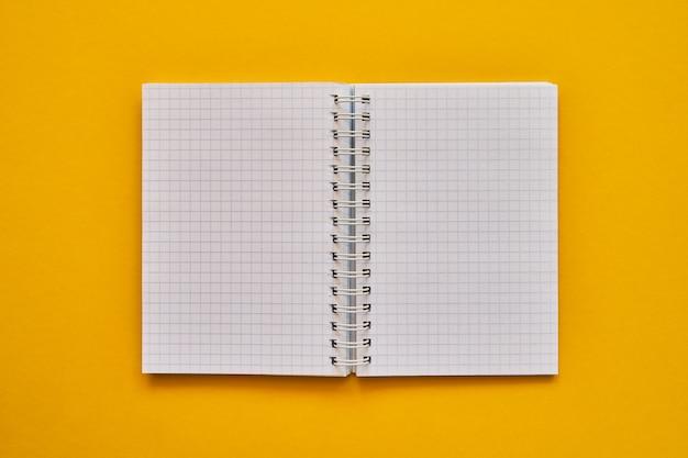 Vista dall'alto del quaderno aperto con pagine bianche. quaderno di scuola su uno sfondo giallo, blocco note a spirale