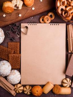 Vista dall'alto del quaderno con diversi biscotti intorno su sfondo scuro