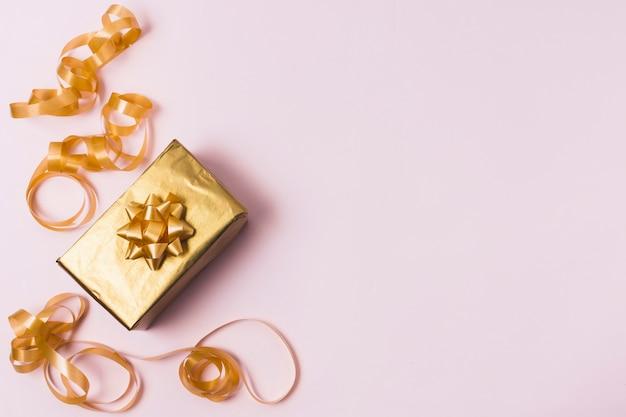 Vista dall'alto del regalo d'oro con nastro