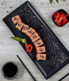Vista dall'alto del rotolo di sushi di salmone servito con salsa di zenzero, wasabi e soia