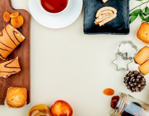 Vista dall'alto del rotolo tagliato e tranciato con prugne secche cupcake sul tagliere con marmellata di tè pesca uvetta biscotti e pigne su superficie bianca con spazio di copia