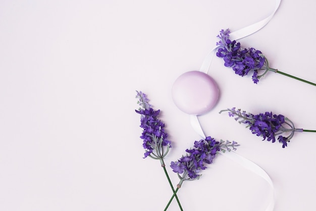 Vista dall'alto del sapone; fiori di lavanda e nastro su sfondo colorato