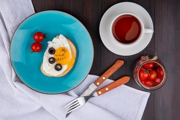 Vista dall'alto del set colazione con uovo fritto oliva e pomodori nel piatto con forchetta e coltello su stoffa e ciotola di pomodoro con tazza di tè su legno