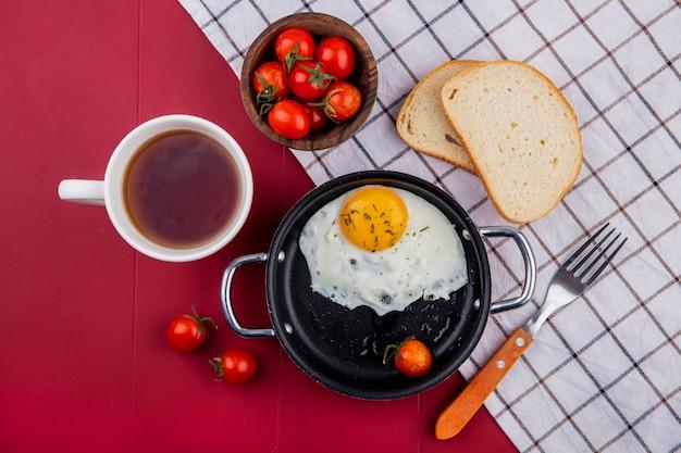 Vista dall'alto del set da colazione con padella di uovo fritto e pomodoro con ciotola di fette di pane al pomodoro forcella su panno plaid e tazza di tè su rosso