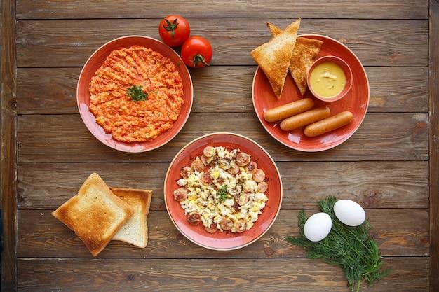 Vista dall'alto del setup della colazione con piatti a base di uova e pomodoro e salsicce