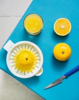Vista dall'alto del succo di lime dolce con spremiagrumi manuale sulla scrivania blu