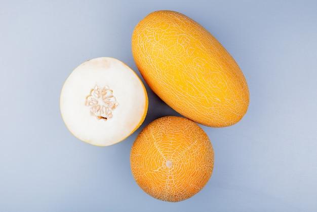 Vista dall'alto del taglio e interi meloni su sfondo grigio bluastro