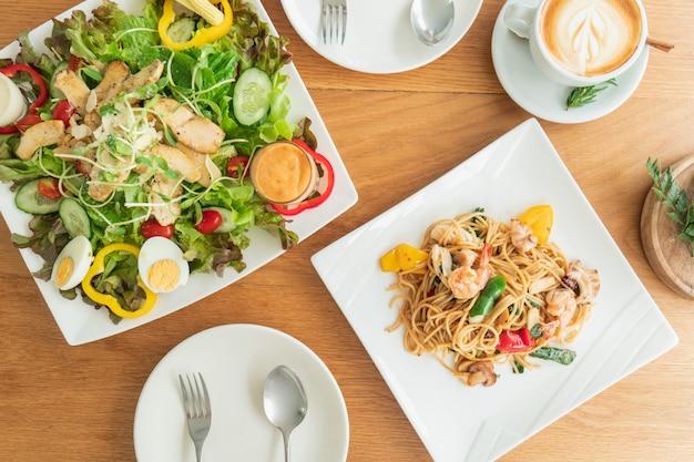 Vista dall'alto del tavolo che viene preparato da un'insalata e spaghetti da mangiare.