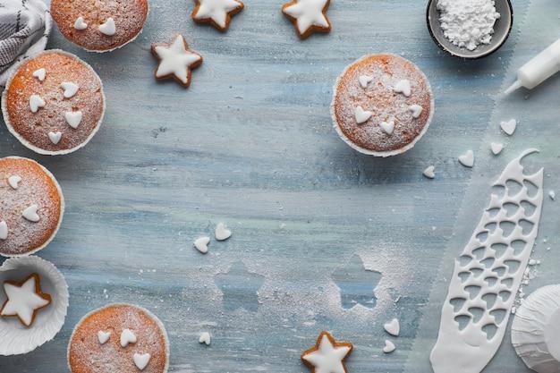 Vista dall'alto del tavolo con muffin zuccherati, glassa fondente e biscotti con stelle di natale sul blu