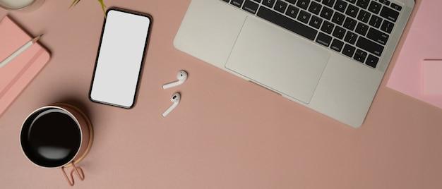 Vista dall'alto del tavolo da lavoro femminile con smartphone, laptop, accessori, tazza di caffè e spazio di copia