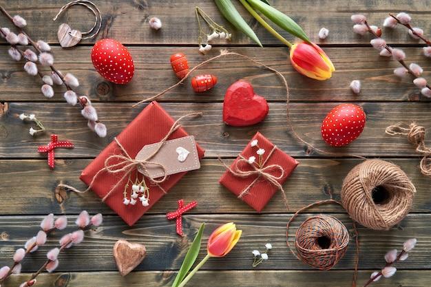 Vista dall'alto del tavolo di legno con decorazioni di primavera, regali avvolti, fiori di salice e tulipano e uova di pasqua