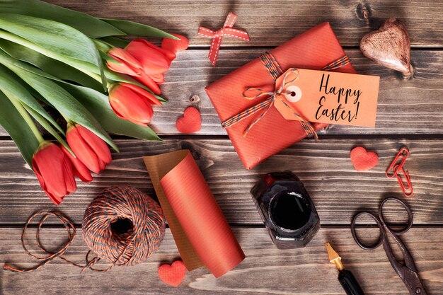 Vista dall'alto del tavolo di legno con decorazioni di primavera, regali avvolti, fiori di tulipano rosso e uova di pasqua