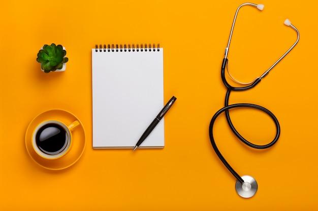Vista dall'alto del tavolo di un medico con blocco note e penna stetoscopio, tastiera, prescrizione e pillole, una tazza di caffè su uno sfondo giallo
