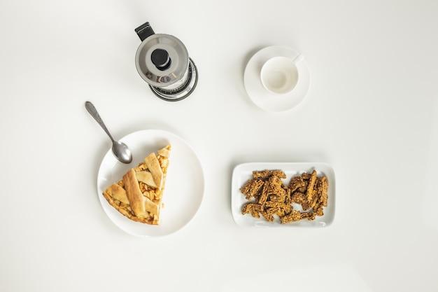 Vista dall'alto del tavolo minimalista con pranzo di lavoro con caffè, cereali e torta di mele.