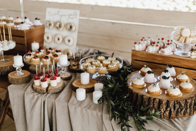 Vista dall'alto del tavolo pieno di dolci deliziosi, cupcakes, ciambelle e panna cotta