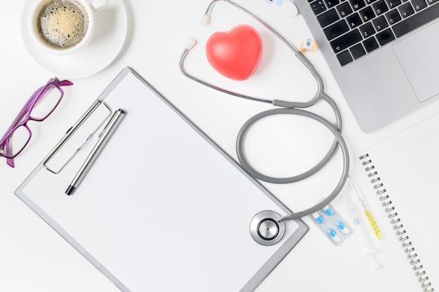 Vista dall'alto del tavolo scrivania del medico con lo stetoscopio