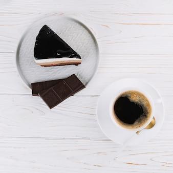 Vista dall'alto del tè; deliziosa pasticceria con barretta di cioccolato per colazione a tavola