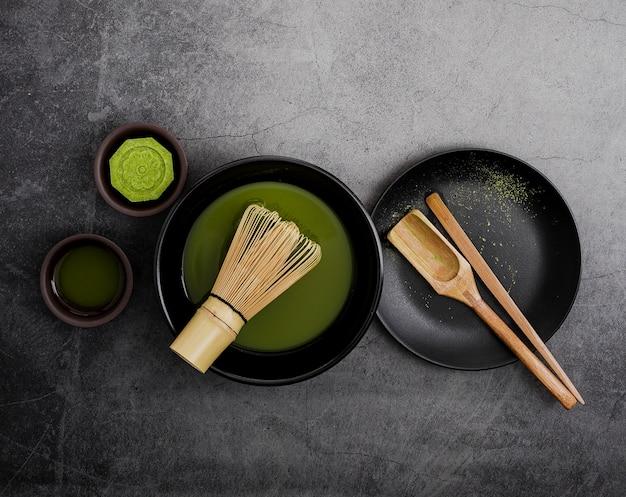 Vista dall'alto del tè matcha in ciotola con frusta di bambù e paletta in legno