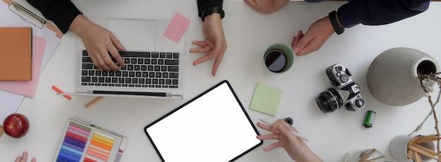 Vista dall'alto del team di designer che lavorano insieme in una sala riunioni minimale con tablet mock-up, laptop, fotocamera e materiali di consumo