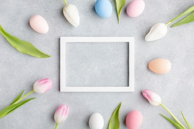Vista dall'alto del telaio con uova di pasqua colorate e tulipani