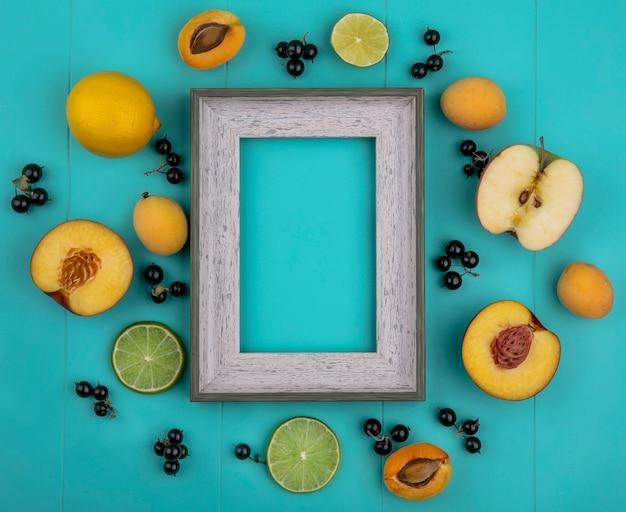 Vista dall'alto del telaio grigio con albicocche mele limone con ribes nero con fettine di lime su una superficie azzurra