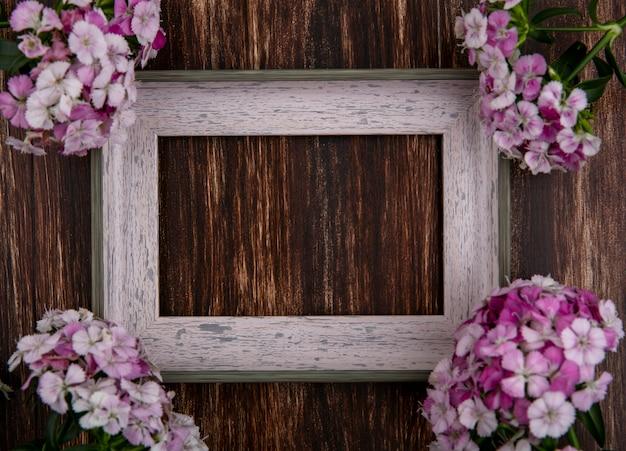 Vista dall'alto del telaio grigio con fiori rosa chiaro su una superficie di legno