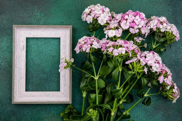 Vista dall'alto del telaio grigio con fiori rosa chiaro su una superficie verde
