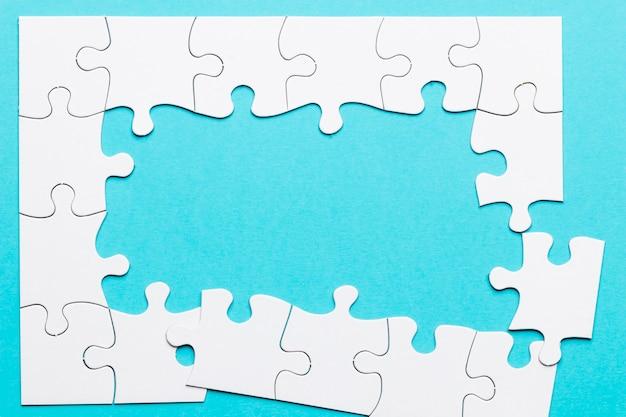 Vista dall'alto del telaio incompleto puzzle su sfondo blu