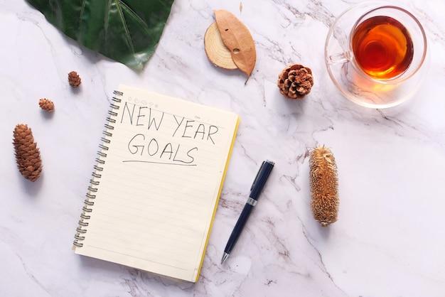 Vista dall'alto del testo degli obiettivi del nuovo anno sul blocco note.