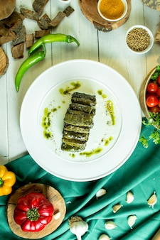 Vista dall'alto del tradizionale dolma cucina caucasica con foglie di vite su un piatto