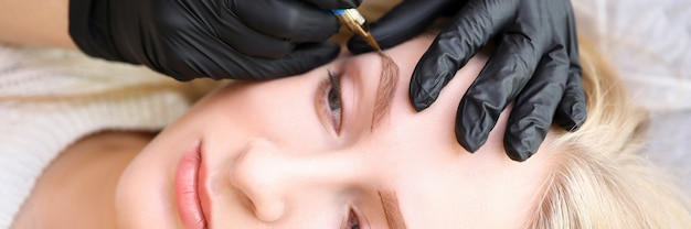 Vista dall'alto del volto femminile all'appuntamento dei cosmetologi. mani del truccatore che applicano pittura sul sopracciglio. trattamento di cura della pelle. procedura professionale di bellezza e concetto di barra sopracciglia