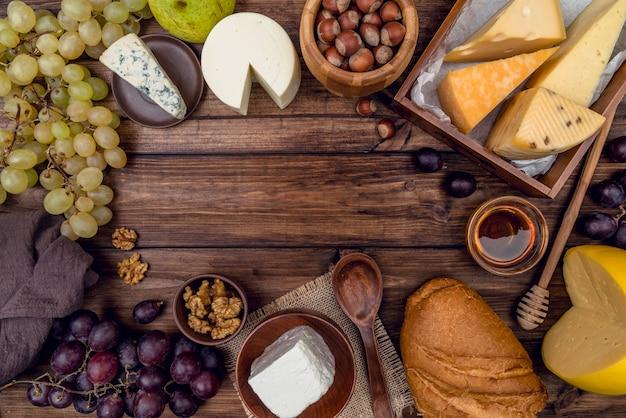 Vista dall'alto deliziosa varietà di formaggi con pane e uva